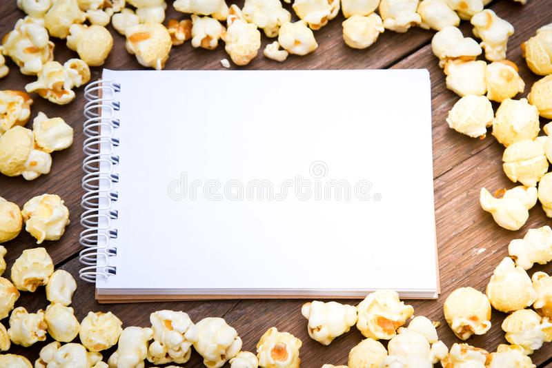Uma bacia de pipoca e de caderno em uma tabela de madeira fotos de stock