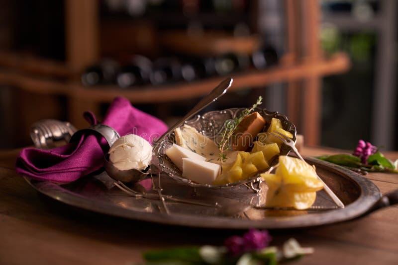 Uma bacia de queijo do mascarpone em uma colher para o gelado em uma bandeja velha, ao lado de um prato com queijo azul, st de Br imagens de stock royalty free