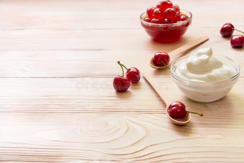 Uma bacia do iogurte grego perto da cereja fresca e adoçada frutifica, espaço da cópia foto de stock royalty free