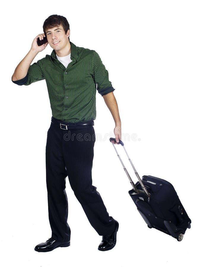 Uma bagagem carreg do homem novo no telefone fotografia de stock