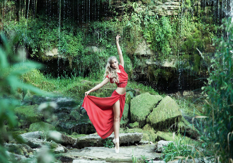 Uma bailarina bonita em uma dança vermelha do vestido na floresta fotos de stock royalty free