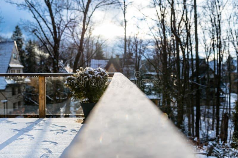 Uma balaustrada coberto de neve, de madeira no balcão com foco seletivo No fundo, nas construções borradas e nas árvores foto de stock royalty free