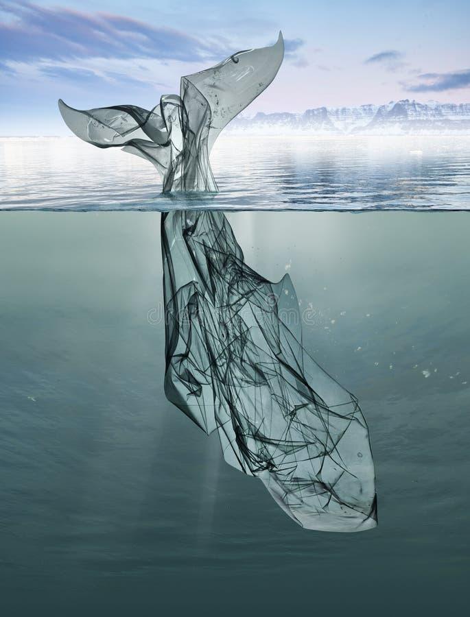 Uma baleia do plástico do lixo que flutua no oceano fotografia de stock royalty free