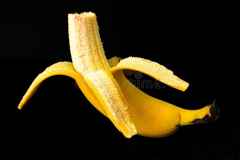 Uma banana descascada no fundo preto fotografia de stock royalty free
