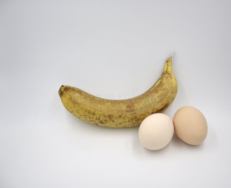 Uma banana e dois ovos marrons imagens de stock