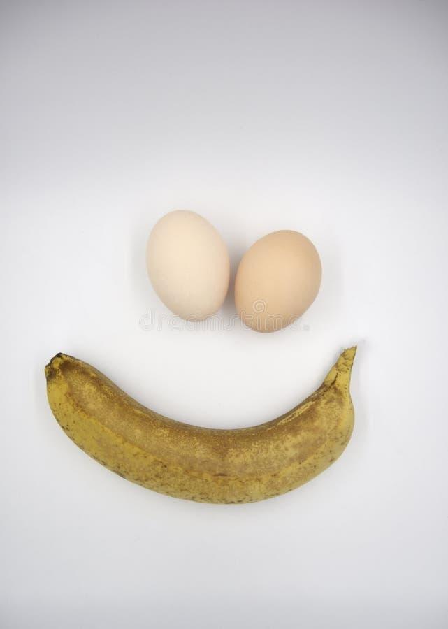 Uma banana e dois ovos marrons foto de stock