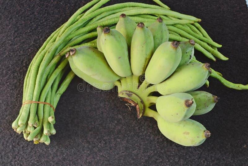 Uma banana e uns feijões longos foto de stock