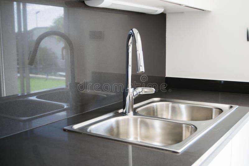 Uma banca da cozinha de aço inoxidável da bacia dobro em um projeto moderno imagens de stock