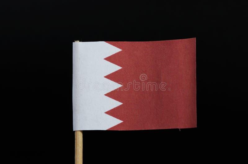 Uma bandeira nacional de Barém no palito no fundo preto Um campo branco no lado da grua separado de um campo vermelho maior sobre imagens de stock