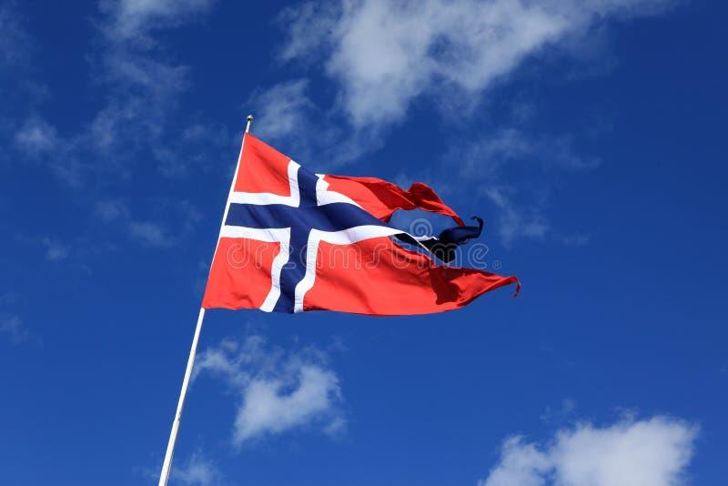 Uma bandeira norueguesa que funde no vento contra o céu azul com nuvem fotografia de stock royalty free
