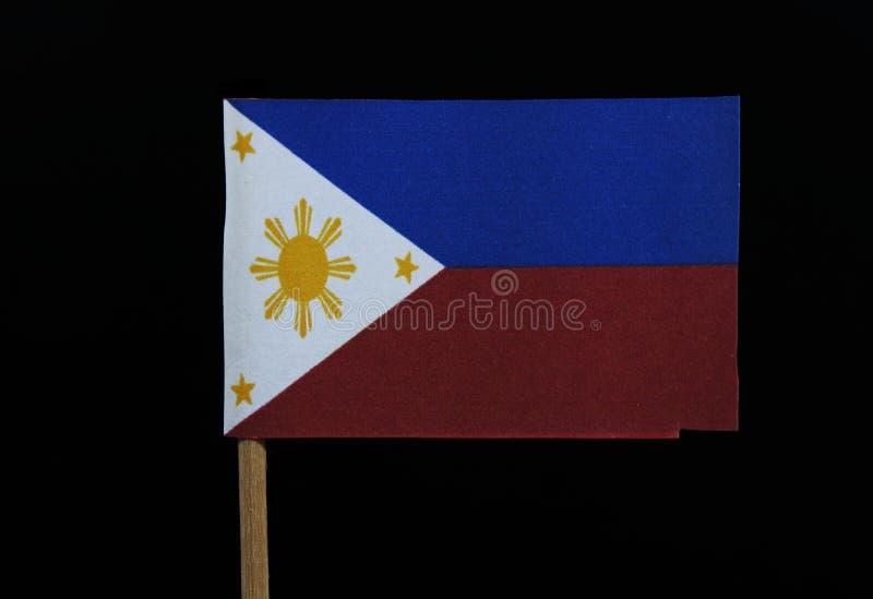 Uma bandeira oficial das Filipinas no palito no fundo preto Um bicolor horizontal de azul e de vermelho com um branco foto de stock
