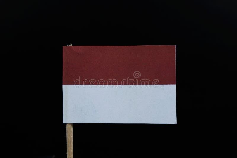 Uma bandeira oficial de Indonésia no fundo preto no palito de madeira Um bicolor horizontal de vermelho e de branco fotografia de stock