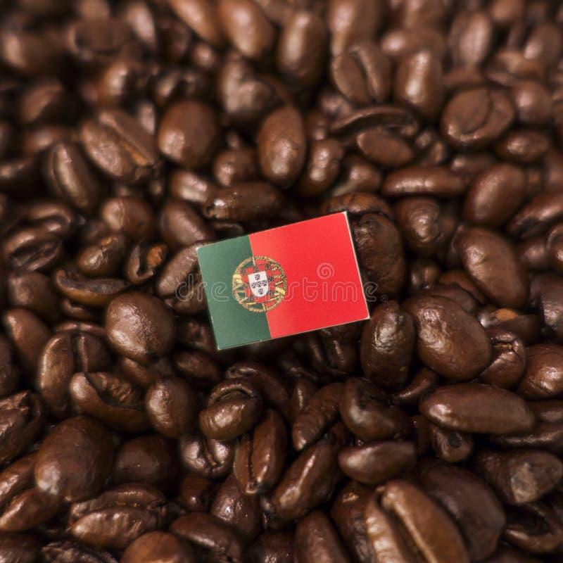 Uma bandeira portuguesa colocada sobre feijões de café roasted foto de stock royalty free