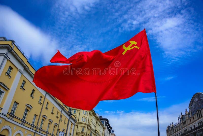 Uma bandeira vermelha da União das Repúblicas Socialistas Soviéticas com o martelo e a foice que acenam no vento no dia internaci imagem de stock royalty free