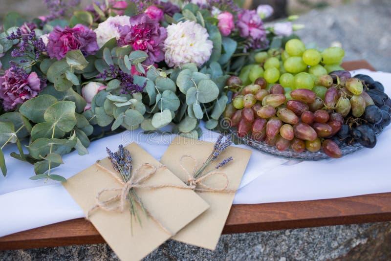 Uma bandeja com convites da uva e do casamento nos envelopes do ofício com alguns ramos da alfazema perto da composição da flor W fotos de stock royalty free