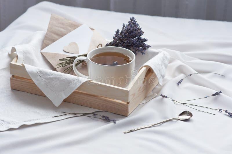 Uma bandeja com um copo da carta de amor quente do chá e da alfazema na cama Café da manhã quente da mensagem do amor do humor da imagem de stock