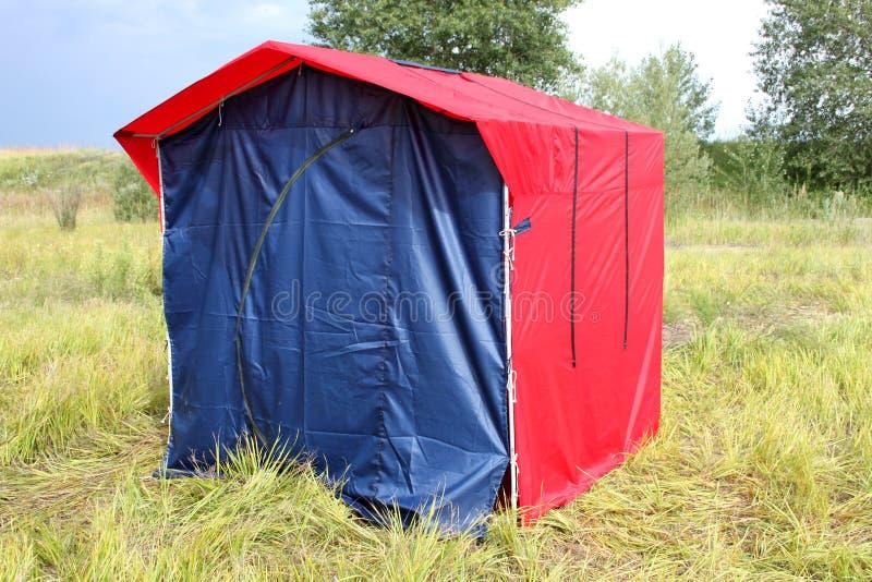Uma barraca caseiro vermelho-azul em um piquenique em uma floresta na grama fotos de stock