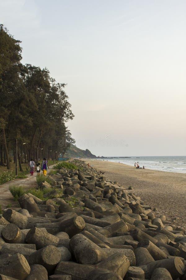 Uma barreira do passeio e do tsunami do mar contra um Sandy Beach, umas árvores verdes e o oceano fotografia de stock