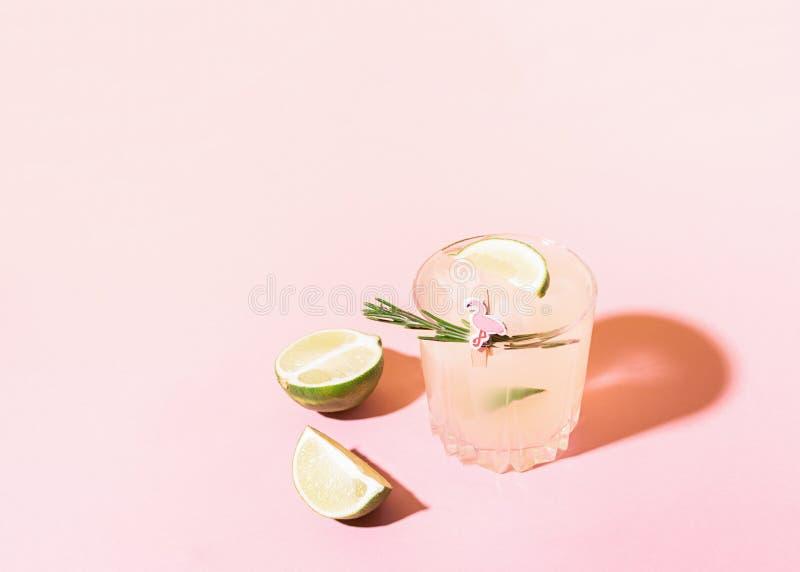 Uma bebida de refrescamento do vidro transparente da limonada do limão e do cal em uma luz solar brilhante do fundo do rosa Cockt imagens de stock royalty free
