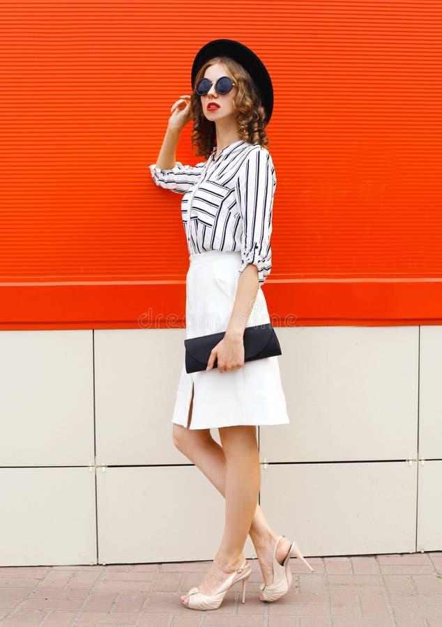 Uma bela jovem de comprimento inteiro, vestida camisa listrada branca, embreagem de bolsa preta, chapéu redondo, saia na rua da c foto de stock royalty free