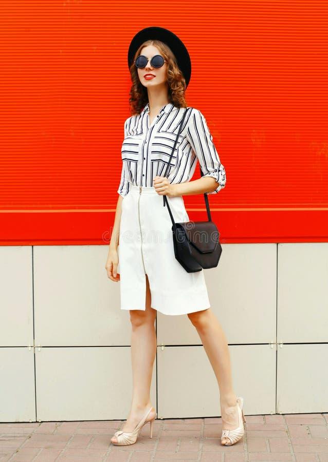 Uma bela jovem de comprimento inteiro, vestida camisa listrada branca, embreagem de bolsa preta, chapéu redondo, saia na rua da c fotos de stock royalty free