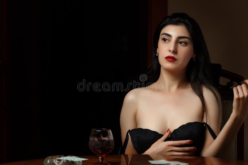 Uma bela morena com lábios escarlate em lingerie negra se senta em uma mesa e se despia depois de perder nas cartas fotografia de stock