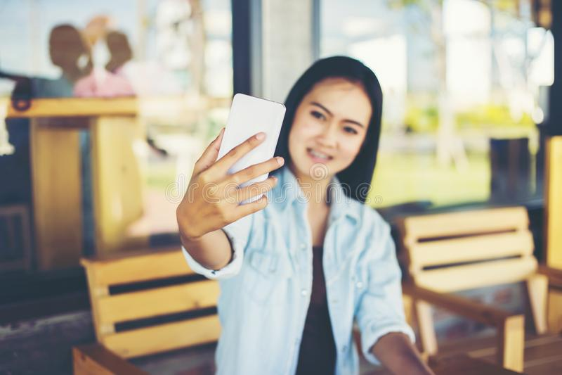 Uma bela mulher usando um vestido branco usando um celular em um café fotografia de stock