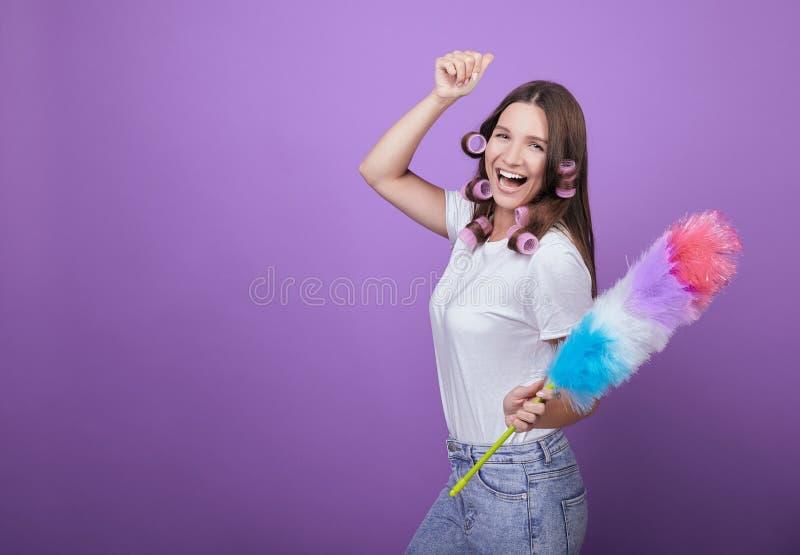 Uma beleza jovem em curlers canta canções e dança enquanto limpa imagem de stock royalty free