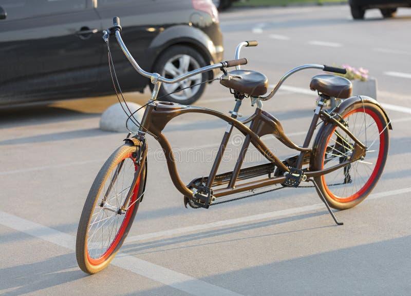 Uma bicicleta em tandem com escarlate das bordas da roda é estacionada em um parque de estacionamento no sol da noite imagens de stock