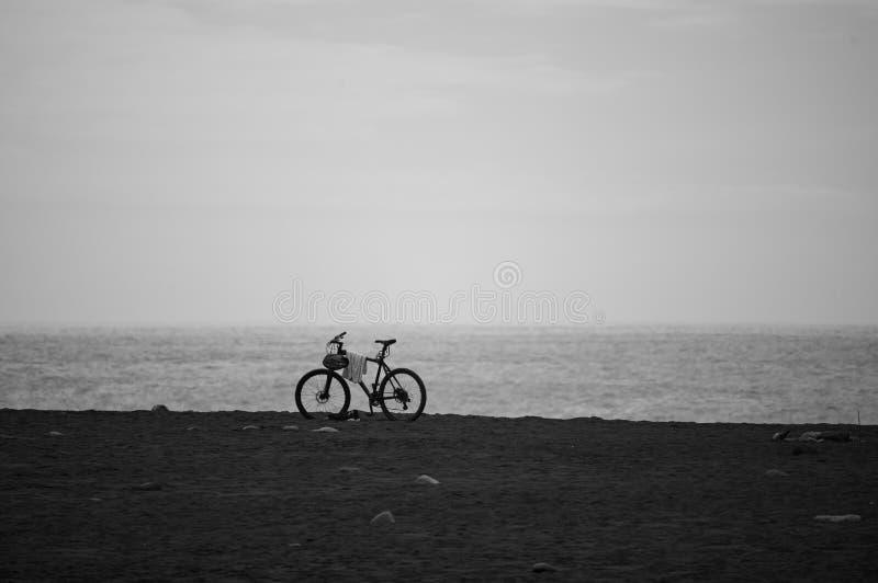 Uma bicicleta está estando na praia imagem de stock royalty free
