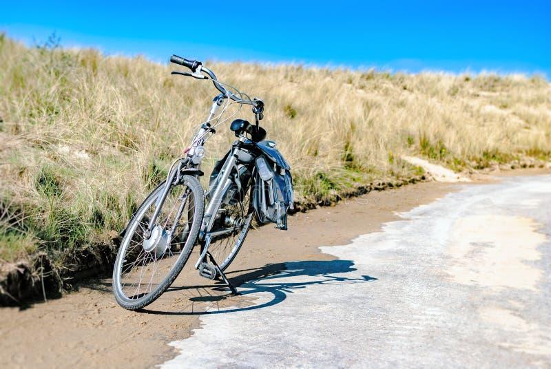 Uma bicicleta estacionada ao longo de uma estrada litoral com as dunas no fundo Conceito do verão férias Arrendamento da biciclet imagem de stock
