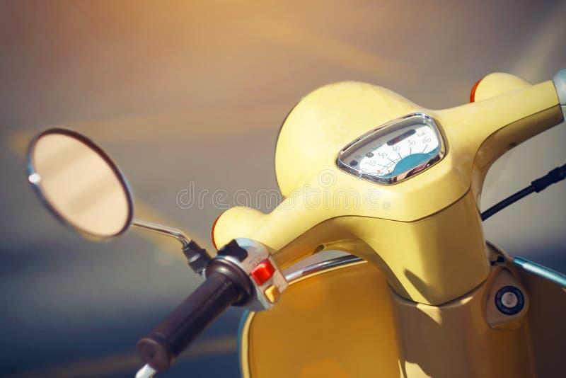 Uma bicicleta motorizada amarela do vintage, que esteja na estrada foto de stock