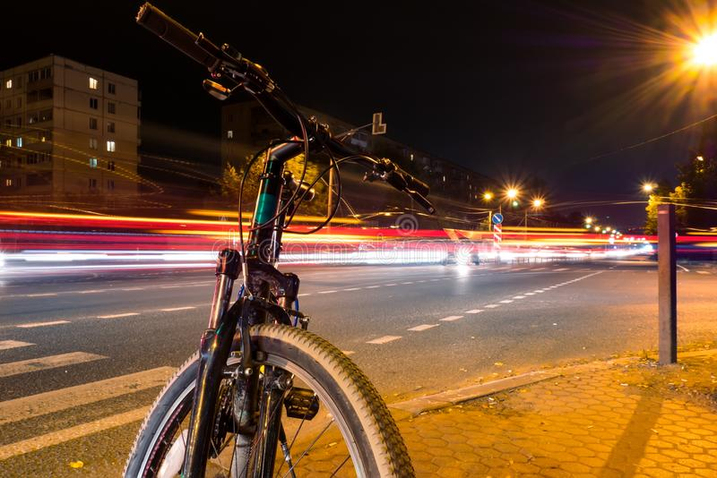 Uma bicicleta na rua em uma noite contra um fundo de luzes obscuras dos carros, a luz arrasta na rua imagem de stock