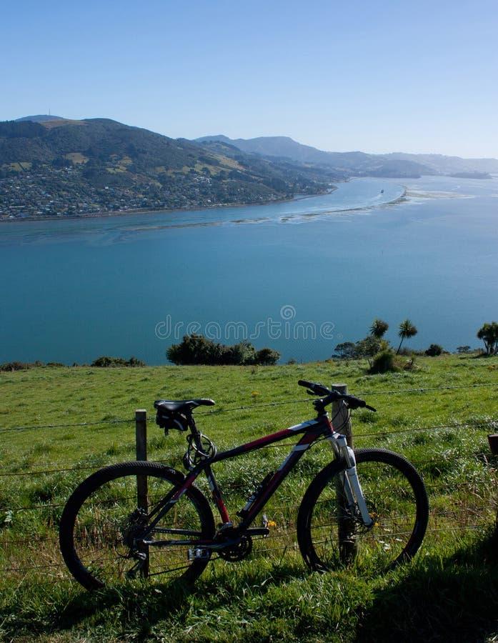 Uma bicicleta que inclina-se contra uma cerca, no fundo uma vista na península de Otago perto de Dunedin em Nova Zelândia em um d foto de stock