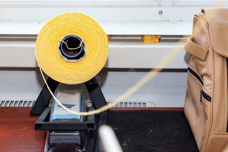 Uma bobina amarela grande com as grandes linhas coloridas de acoplamento no estúdio para a oficina do design de interiores na tab fotos de stock