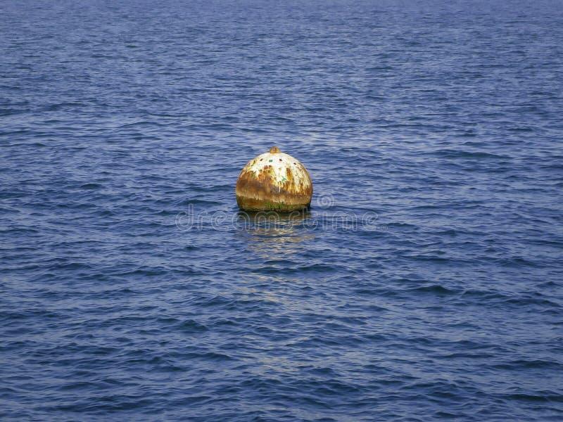 Uma boia que flutua na água azul do oceano fotos de stock