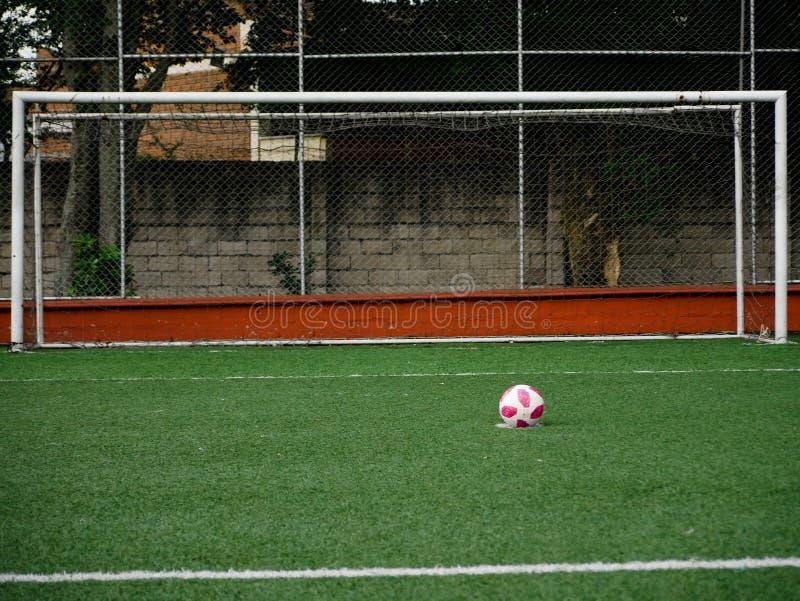 Uma bola de futebol com os pontos cor-de-rosa colocados no ponto do pontapé de grande penalidade sem um no meta foto de stock royalty free