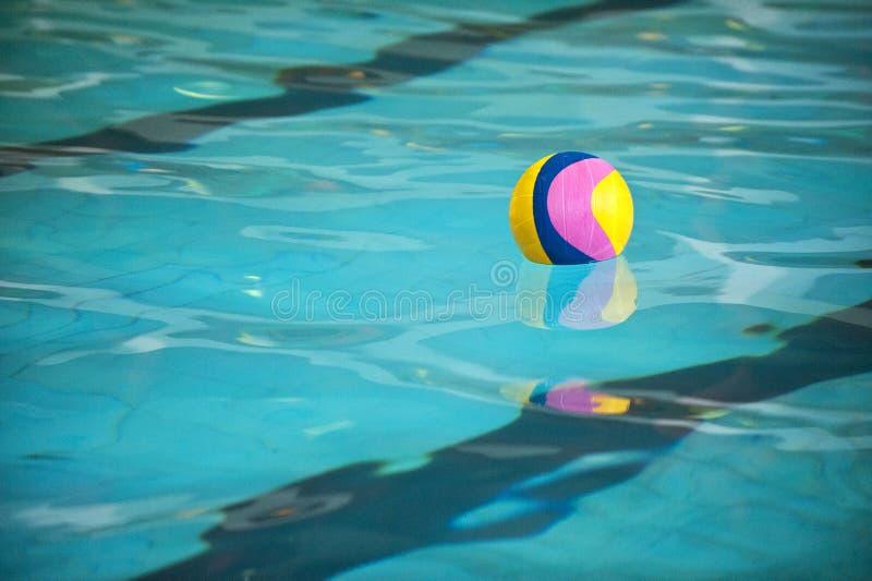 Uma bola de polo aquático que flutua na água em uma associação fotografia de stock royalty free