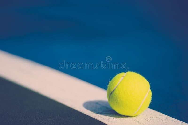 Uma bola de tênis nova na linha diagonal branca na corte dura azul com luz do direito, tom do vintage foto de stock