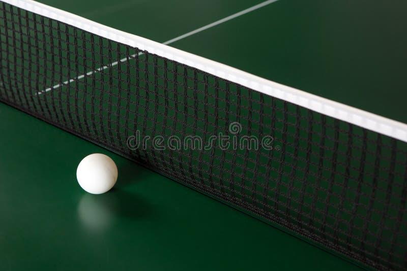 Uma bola de t?nis de mesa em uma tabela verde ao lado da rede imagens de stock royalty free