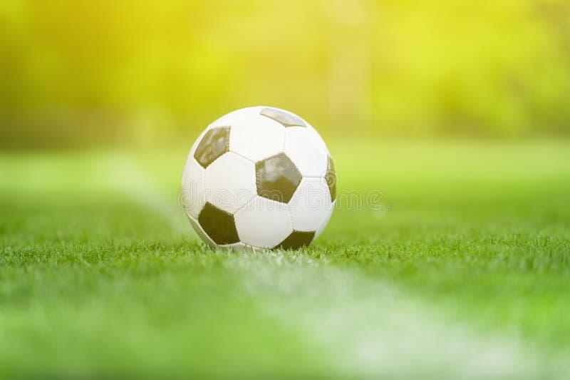 Uma bola para o futebol do futebol da rua sob a luz do raio do por do sol fotos de stock royalty free