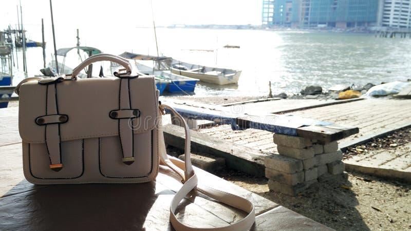 Uma bolsa branca no beira-mar durante o por do sol fotos de stock royalty free