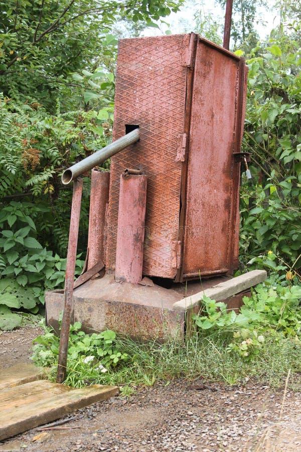 Uma bomba elétrica da água com um fechamento para a água de bombeamento do subterrâneo e o derramamento na embarcação puted nas p fotografia de stock