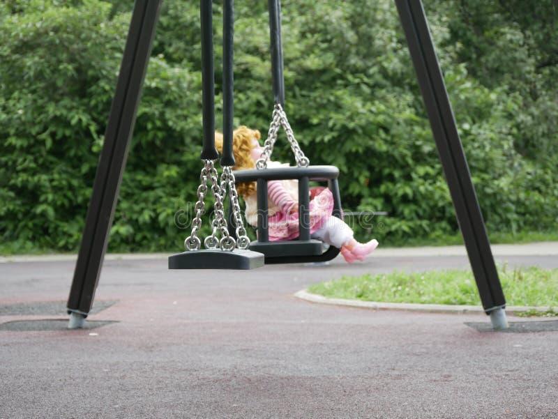 Uma boneca bonita em um balanço das crianças em um parque da cidade em um dia de verão ensolarado foto de stock royalty free
