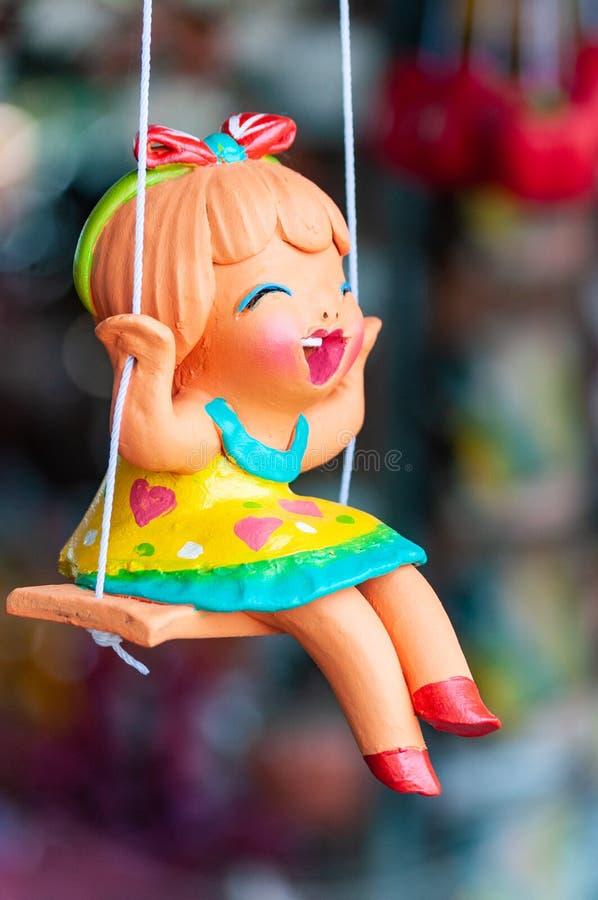 Uma boneca cerâmica em um balanço foto de stock