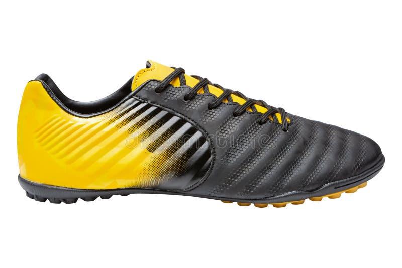 Uma bota do futebol, cor amarela combinada com as pretas, sapatas dos esportes, em um fundo branco fotografia de stock