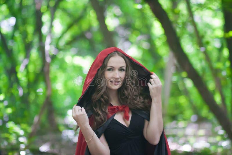 uma bruxa em um chapéu vermelho no meio imagem de stock