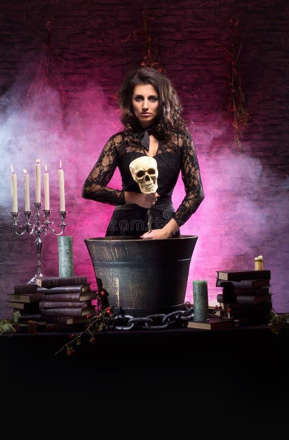 Uma bruxa triguenha 'sexy' que faz o veneno fotografia de stock royalty free