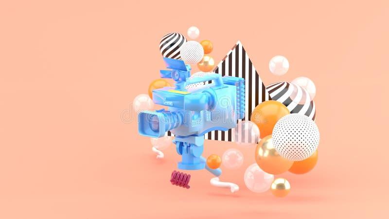 Uma câmara de vídeo azul cercada por bolas coloridas em um fundo cor-de-rosa imagens de stock royalty free