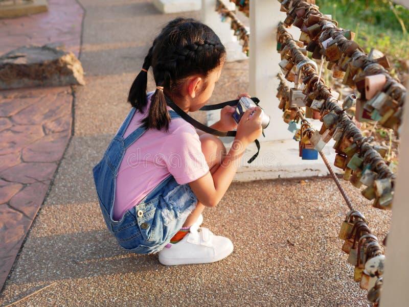 Uma câmera da terra arrendada da menina com tomada de uma imagem Criança asiática que faz a viagem da foto imagens de stock